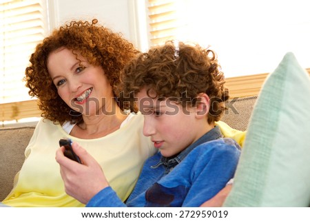 Portrait of a cheerful mother sitting next to her son who is playing games on his phone - stock photo