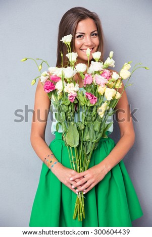 Portrait of a cheerful pretty woman holding flowers over gray background. Looking at camera - stock photo