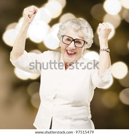 portrait of a cheerful senior woman gesturing victory against a abstract background - stock photo