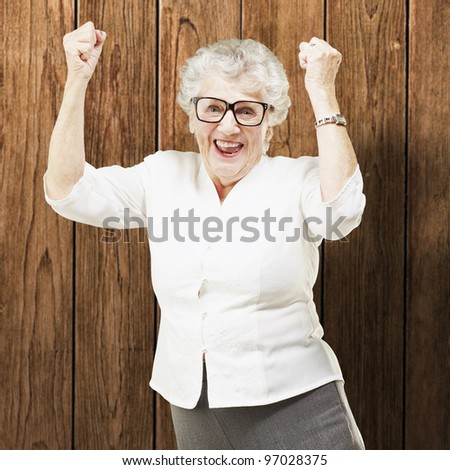 portrait of a cheerful senior woman gesturing victory against a wooden wall - stock photo