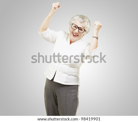 portrait of a cheerful senior woman gesturing victory over a grey background - stock photo