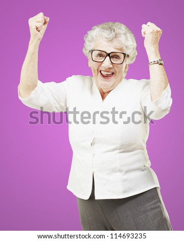 portrait of a cheerful senior woman gesturing victory over pink background