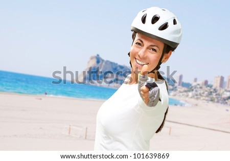 portrait of a cheerful sporty middle aged woman doing a victory symbol near the beach - stock photo