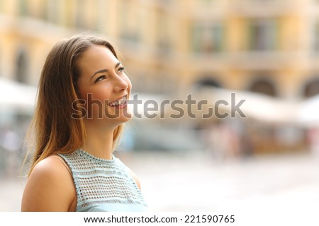 Portrait of a cheerful tourist woman looking at side in a touristic place in vacations - stock photo