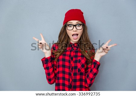 Portrait of a cheerful trendy woman showing two fingers sign over gray background - stock photo