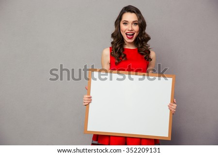 Portrait of a cheerful woman holding blank board over gray background - stock photo