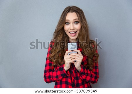 Portrait of a cheerful woman holding smartphone and looking at camera over gray background - stock photo