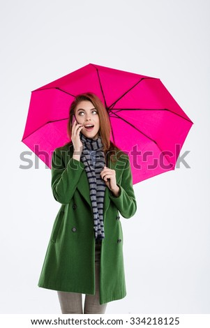 Portrait of a cheerful woman holding umbrella and talking on the phone isolated on a white background - stock photo