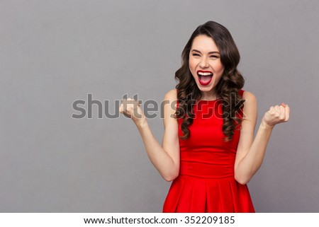 Portrait of a cheerful woman in red dress celebrating her success over gray background - stock photo