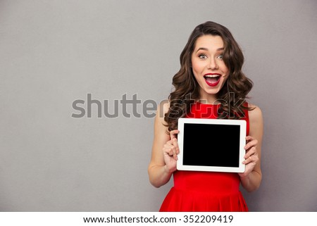 Portrait of a cheerful woman in red dress showig blank tablet computer screen over gray background - stock photo