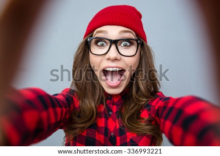 Portrait of a cheerful woman making selfie photo over gray background - stock photo