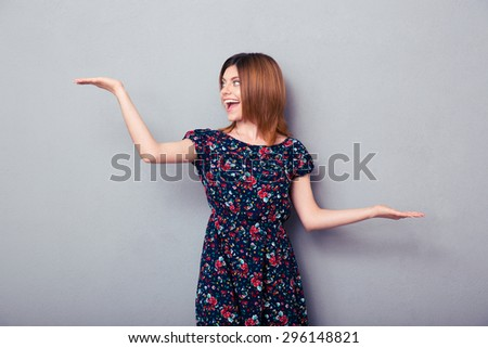 Portrait of a cheerful woman presenting copyspace on palms over gray background. Looking away - stock photo