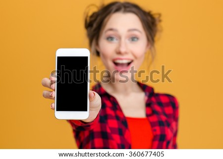 Portrait of a cheerful woman showing blank smartphone screen over yellow background. Focus on smartphone - stock photo