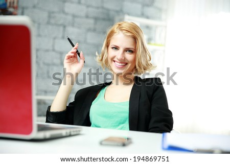 Portrait of a cheerful woman sitting at the table in office - stock photo