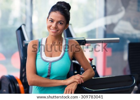 Portrait of a cheerful woman standing in fitness gym - stock photo
