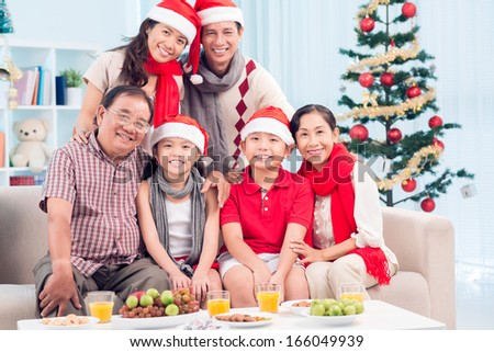 Portrait of a cheerful Xmas family bonding and posing at camera - stock photo