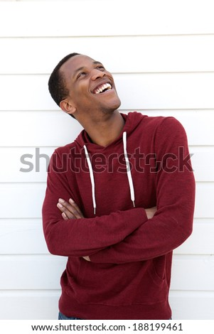 Portrait of a cheerful young african american man laughing and looking up - stock photo