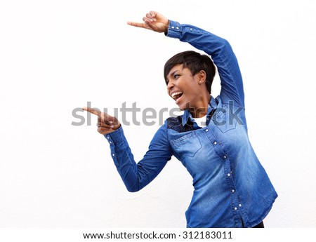 Portrait of a cheerful young african american woman pointing fingers - stock photo