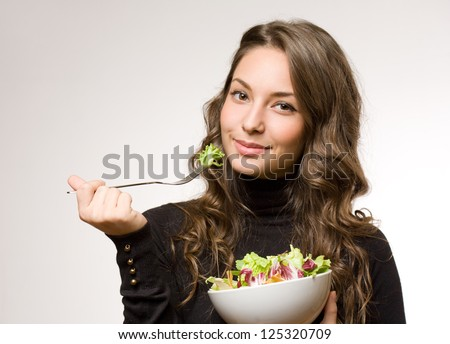 Portrait of a cheerful young brunette woman having salad.