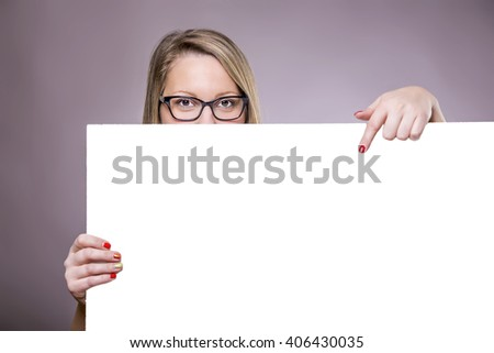 Portrait of a cheerful young caucasian woman holding a white blank banner. - stock photo