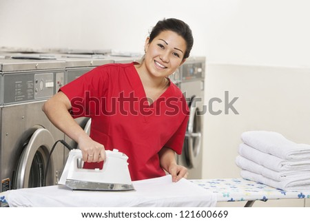 Portrait of a cheerful young employee ironing in Laundromat - stock photo