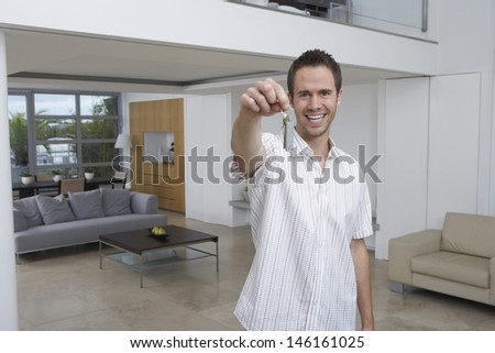 Portrait of a cheerful young man holding key in new home