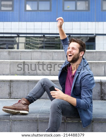 Portrait of a cheerful young man holding mobile phone - stock photo