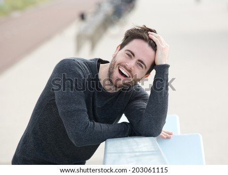 Portrait of a cheerful young man laughing with hand in hair  - stock photo
