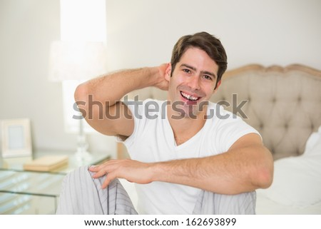 Portrait of a cheerful young man sitting in bed at home - stock photo