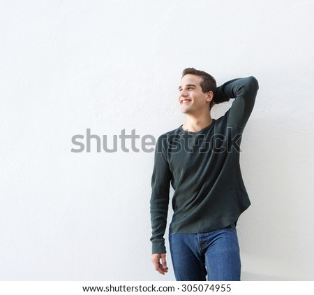 Portrait of a cheerful young man standing against white background - stock photo