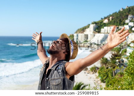 Portrait of a cheerful young man with arms spread open at the beach  - stock photo