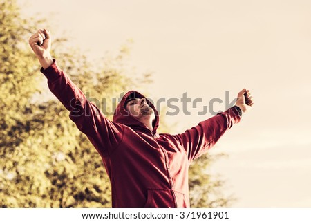 Portrait of a cheerful young man with arms spread open outdoors retro style photo  - stock photo