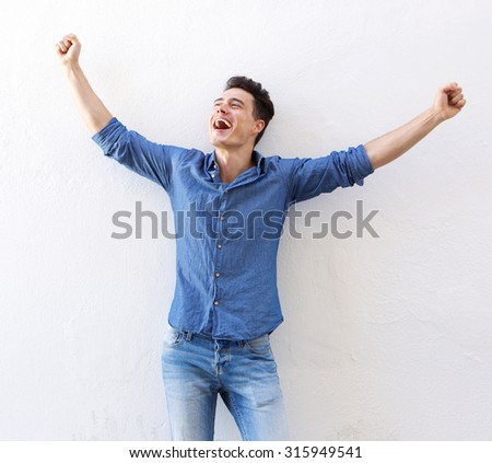 Portrait of a cheerful young man with raised arms celebrating - stock photo
