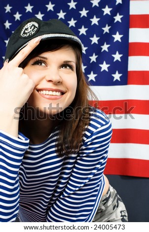 portrait of a cheerful young sailor standing opposite an American flag - stock photo