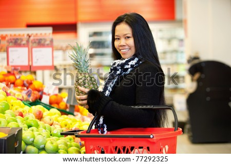 Portrait of a cheerful young woman buying fruits in the supermarket - stock photo