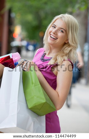 Portrait of a cheerful young woman carrying shopping bags - stock photo