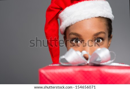 Portrait of a cheerful young woman in Santa hat looking at camera behind a x-mas giftbox on the foreground - stock photo