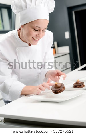 portrait of a cheerful young woman professional pastry cook at work in kitchen decorating a chocolate dessert - stock photo