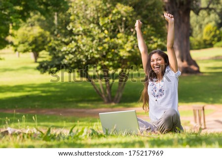 Portrait of a cheerful young woman raising hands with laptop in the park