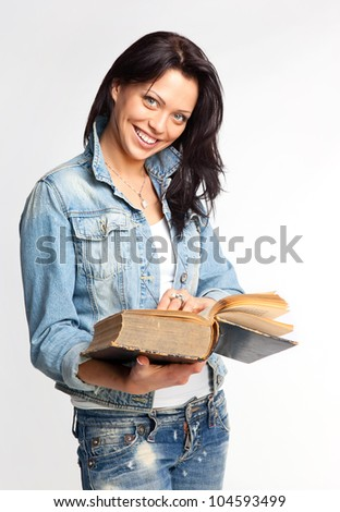 Portrait of a cheerful young woman reading a book - stock photo