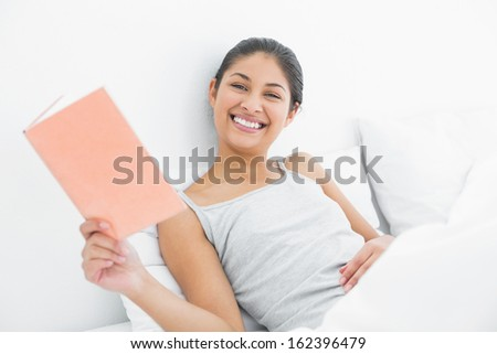 Portrait of a cheerful young woman reading a book in bed at home - stock photo