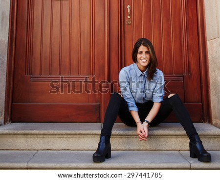Portrait of a cheerful young woman smiling to the camera while sitting on urban stairs with brown wooden door background with copy space for your text message or content,hipster girl resting outdoors - stock photo