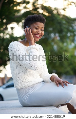 Portrait of a cheerful young woman talking on cell phone outside - stock photo