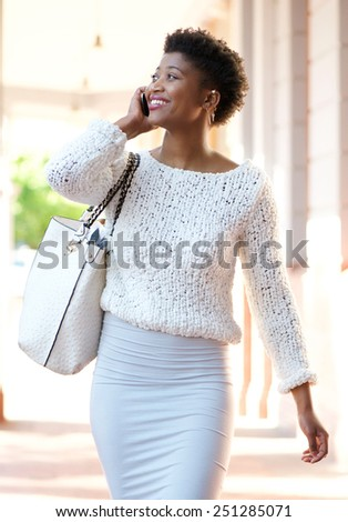 Portrait of a cheerful young woman walking and calling by mobile phone - stock photo