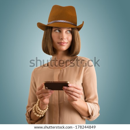 Portrait of a cheerful young woman wearing hat using her smartphone - stock photo