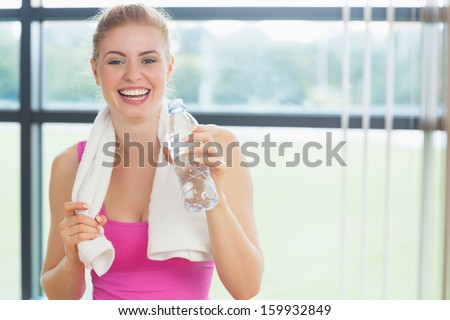 Portrait of a cheerful young woman with towel around neck holding water bottle in fitness studio - stock photo