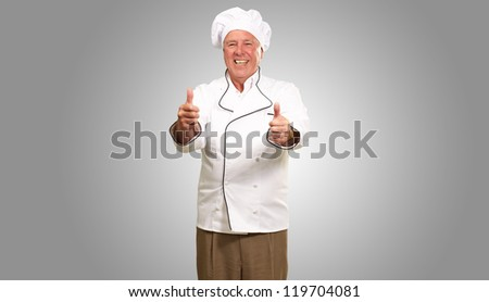 Portrait Of A Chef Cook With Hand Sign On Gray Background - stock photo
