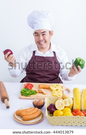 Portrait of a chef holding fruit and vegetable isolated on white background