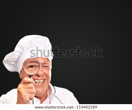 Portrait Of A Chef Holding Magnifying Glass Isolated On Black Background - stock photo