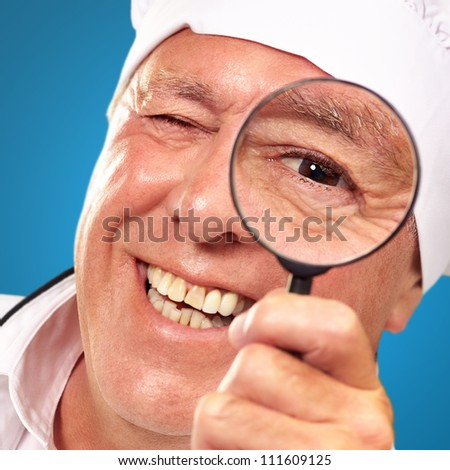 Portrait Of A Chef Holding Magnifying Glass Isolated On Blue Background - stock photo